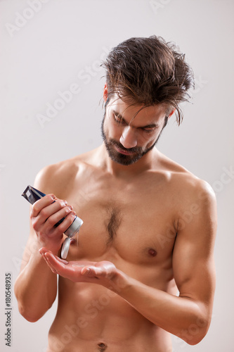 Fotobehang Kapsalon Young man is applying hair gel to his hair.
