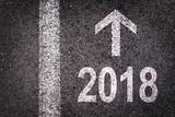2018 and an arrow written on an asphalt road background - 180561965