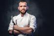 Leinwandbild Motiv Chef cook holds a knife over dark grey background.