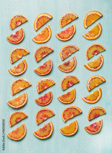 Natural fruit pattern concept. Fresh juicy blood orange slices placed in rows over light blue painted table background, top view - 180568561