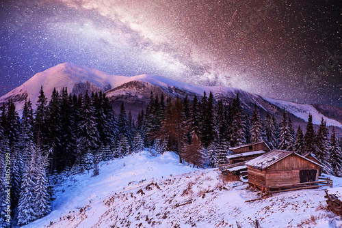 Fotobehang Purper magical winter snow covered trees and mountain village. Winter landscape. Vibrant night sky with stars and nebula and galaxy.