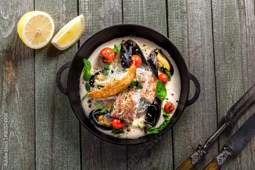 Fototapeta Delicious Asian meal made of sea bass fish, mussels, crab meat and other seafood with tomato and rice noodles on a rustic wooden table. Top view.