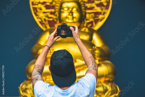 Fotobehang Boeddha Man holding a camera and take a photo of a golden buddha
