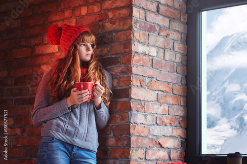 Poster A woman holds coffee and looking over the window on a winter mou