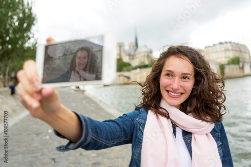 Sticker Young woman on holidays in Paris taking selfie in front on Notre Dame - Tourism concept