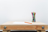 wooden child drawing table with color pencils by the white wall - 180586352