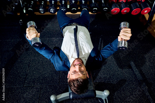 Poster Businessman doing exercises with dumbbells in the gym.