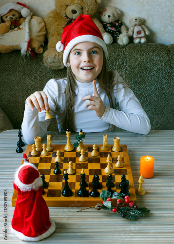 Plakat Cheerful girl in a Christmas hat and plays chess with Santa Claus