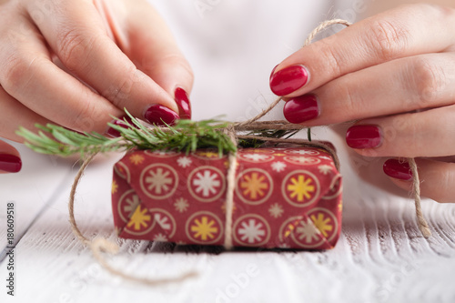 Fototapeta red gift box in female hands. Christmas background