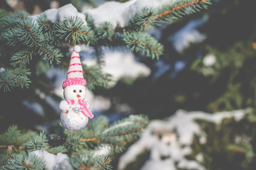 Christmas background Snowman sitting on snow-covered branches of a Christmas tree