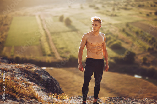 Fotobehang Diepbruine Young sportive man posing on nature