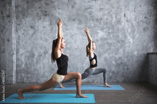 Pair sporty yoga women doing exercise on gray stylish background.