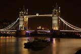 Most Tower Bridge w Londynie, Wielka Brytania, oświetlony kolorowo nocą, na Tamizie dwie niewyraźnie łodzie, barki, długie naświetlanie - 180615337
