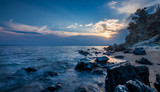 Beautiful sunset near the sea with waves over the rocks