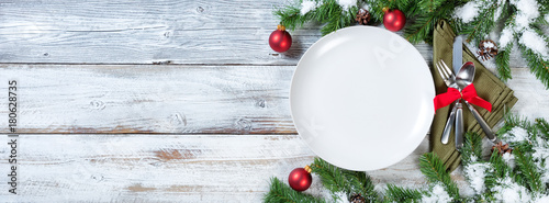 Christmas Table place setting on rustic white wood with snow tipped fir branches