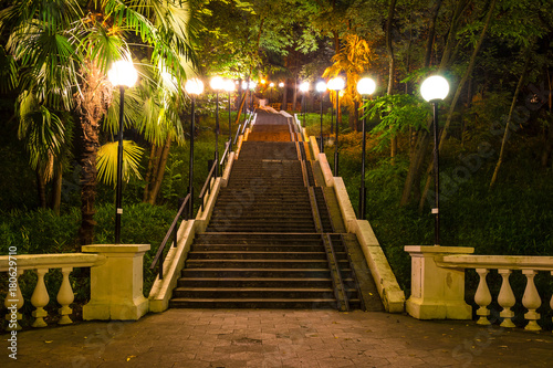 Night view of illuminated high staircase surrouded by thicket of different trees on Tonnelnaya street, Sochi, Russia