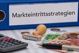 Aktenordner (blau) mit Beschriftung Markteintrittsstrategien