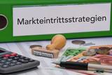 Aktenordner (grün) mit Beschriftung Markteintrittsstrategien