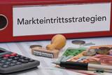 Aktenordner (rot) mit Beschriftung Markteintrittsstrategien