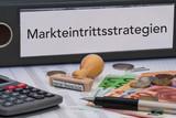 Aktenordner (schwarz) mit Beschriftung Markteintrittsstrategien