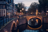 A bridge, canal, and historic houses during twilight blue hour, Amsterdam, Netherlands