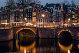 Old historic houses, canal, bridge and a yellow light trail during twilight blue hour, Amsterdam, Netherlands - 180639586