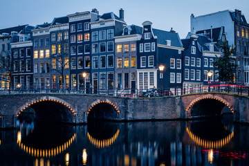 Old historic houses, canal, bridge and a red light trail during twilight blue hour, Amsterdam, Netherlands