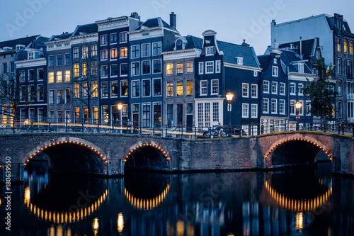Fridge magnet Old historic houses, canal, bridge and a yellow light trail during twilight blue hour, Amsterdam, Netherlands