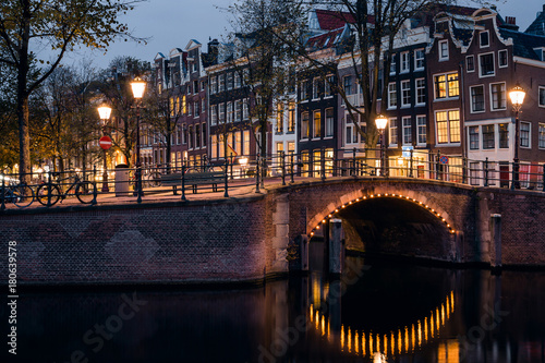 Foto op Plexiglas Amsterdam A bridge, canal, historic houses, and yellow light trail during twilight blue hour, Amsterdam, Netherlands