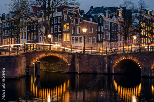 Old historic houses, canal, bridge and a yellow light trail during twilight blue hour, Amsterdam, Netherlands