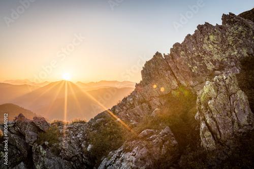 Foto op Plexiglas Ochtendgloren Sonnenaufgang am Berg mit Felsen im Vordergrund