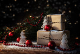 christmas gift boxes in kraft paper decorated with red baubles, fir branches and small wooden trees, some snow and bokeh lights, dark rustic background with copy space - 180644975
