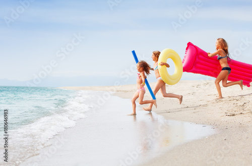 Three happy girls running together in tropical sea