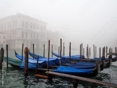 Foto op Plexiglas Venetie Blue covered gondolas moored on a canal in a foggy morning Venice