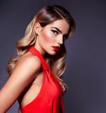 Portret piękna młoda dziewczyna z włosianym tytułowaniem - Hollywood fala w czerwonej sukni w studiu na szarym tle.