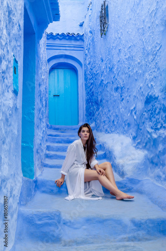 Aluminium Marokko Beautiful girl in a white dress against a blue city Chefchaouen, Morocco