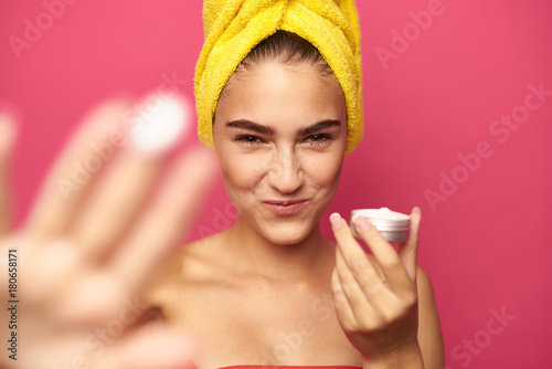 Leinwanddruck Bild young girl with a yellow towel on her head holds a face cream