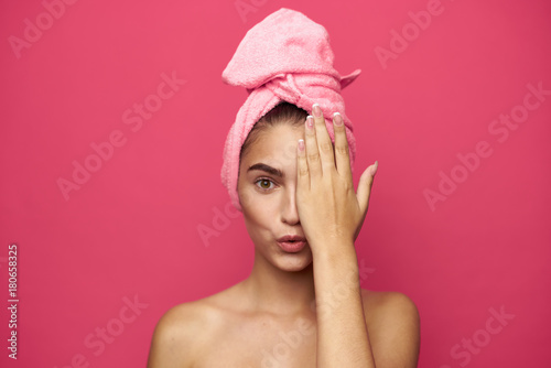 young woman with a towel on her head covers half a person's hand