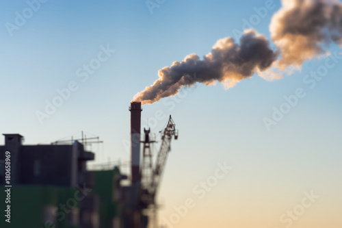 Foto op Plexiglas Kiev Environmental problem of city air pollution - Industrial construction cranes and building site over Steam and smoke emissions. grunge filter photo