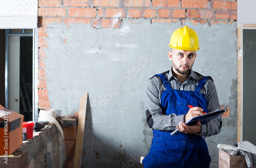 Worker is writing report about work for client at the object. © JackF