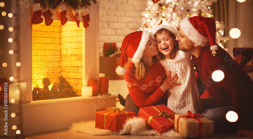 Fototapeta Merry Christmas! happy family mother father and child with gifts near tree