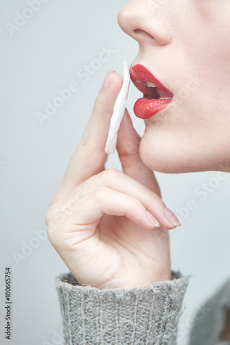 A young girl wipes the red lipstick, close-up Plakat