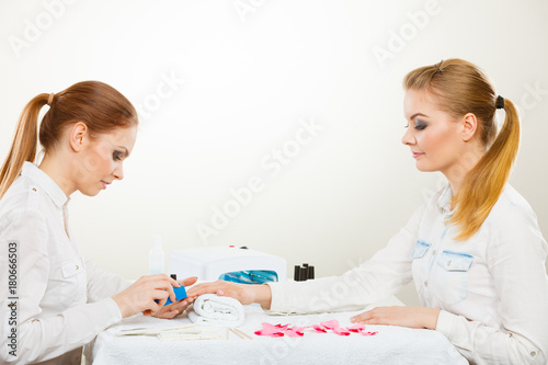 Deurstickers Manicure Beautician with client at beauty salon.