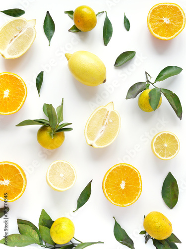 Fototapeta Food pattern of fresh fruit in a cut. Oranges, lemons slices , tangerines with green leaves. Composition from fruits, top view, flat lay. Citrus fruits background, wallpaper.