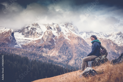 Keuken foto achterwand Zalm Young beautiful active traveler woman admiring the landscape sitting on a rock in the Dolomites, travel, lifestyle, vacations, unity with nature