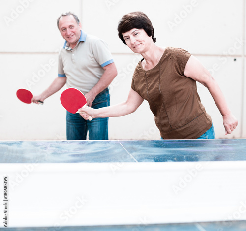 mature man and woman playing table tennis Poster