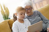 Little girl with grandmother using tablet at home - 180688120