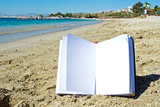 a notebook on the sand