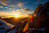 Flags of Tibetan prayers in the mountains with the colors of a warm sunset