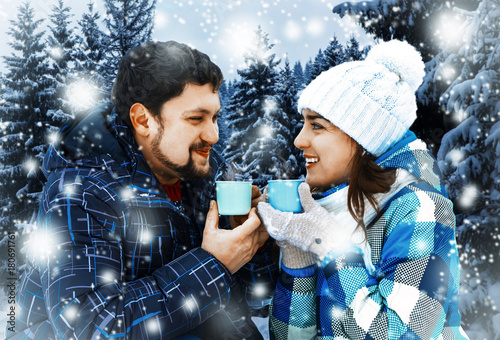 Attractive man with a woman drinking coffee on a background of a Christmas landscape. Winter nature